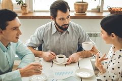 Έξυπνοι συμπαθητικοί νέοι που έχουν τον καφέ από κοινού στοκ φωτογραφίες