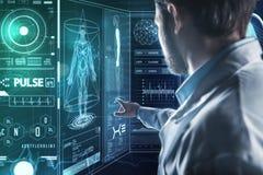 Έξυπνος γιατρός που δείχνει την οθόνη εργαζόμενος με τις σύγχρονες τεχνολογίες Στοκ Εικόνες