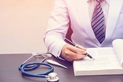 Έξυπνος γιατρός που εγκαθιστά και που διαβάζει το βιβλίο στοκ εικόνες