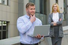 Έξυπνος επιχειρηματίας με το lap-top μπροστά από την επιχειρησιακή κυρία που εξετάζει τον υπαίθρια Στοκ φωτογραφία με δικαίωμα ελεύθερης χρήσης