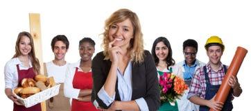Έξυπνος επιχειρησιακός εκπαιδευόμενος θηλυκών με την ομάδα άλλων διεθνών μαθητευόμενων στοκ εικόνες