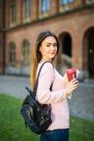 Έξυπνος ευφυής βέβαιος ευτυχής γυαλιών σπουδαστών grad στον πανεπιστημιακό κήπο με την τσάντα και τα βιβλία πίνει τον καφέ υπαίθρ στοκ εικόνες με δικαίωμα ελεύθερης χρήσης