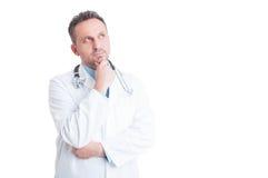 Έξυπνος και όμορφος γιατρός ή γιατρός που σκέφτεται και που αναρωτιέται Στοκ φωτογραφία με δικαίωμα ελεύθερης χρήσης