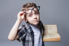 Έξυπνος μαθητής στα γυαλιά με το εγχειρίδιο στα χέρια στοκ φωτογραφία με δικαίωμα ελεύθερης χρήσης
