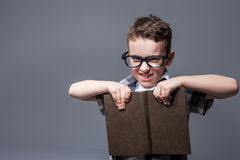 Έξυπνος μαθητής στα γυαλιά με το εγχειρίδιο στα χέρια στοκ εικόνες