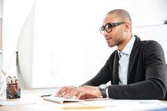 Έξυπνος νέος επιχειρηματίας που εξετάζει τον υπολογιστή Στοκ Φωτογραφία