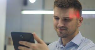 Έξυπνος νέος εργαζόμενος γραφείων διευθυντών γιατρών δικηγόρων επιχειρηματιών προγραμματιστών που εξετάζει το PC ταμπλετών του στ απόθεμα βίντεο