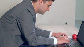 Έξυπνος νεαρός άνδρας σε ένα κοστούμι που λειτουργεί σε έναν υπολογιστή φιλμ μικρού μήκους