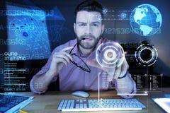 Έξυπνος προγραμματιστής που δαγκώνοντας τα γυαλιά του και δείχνοντας την οθόνη στοκ φωτογραφίες