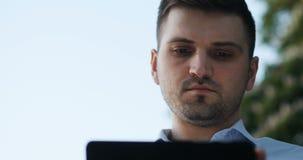 Έξυπνος σοβαρός νεαρός άνδρας που χρησιμοποιεί το PC ταμπλετών του στην οδό, καλοκαίρι φιλμ μικρού μήκους