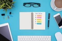 Έξυπνος στόχος που θέτει με τις προμήθειες γραφείων πέρα από το μπλε γραφείο Στοκ φωτογραφία με δικαίωμα ελεύθερης χρήσης