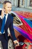Έξυπνος συμπαθητικός επιχειρηματίας που μιλά ένα ακροφύσιο καυσίμων από το αυτοκίνητο Στοκ Φωτογραφίες