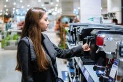Έξυπνος σύγχρονος θηλυκός πελάτης που επιλέγει τη μηχανή καφέ στοκ εικόνες