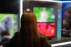 Έξυπνος σύγχρονος θηλυκός πελάτης που επιλέγει τους μεγάλους τηλεοπτικούς δέκτες στοκ εικόνες