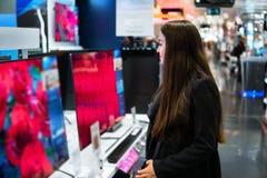 Έξυπνος σύγχρονος θηλυκός πελάτης που επιλέγει τους μεγάλους τηλεοπτικούς δέκτες στοκ φωτογραφία
