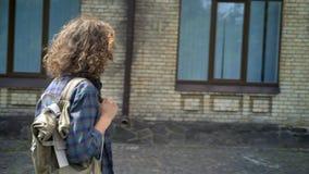Έξυπνος nerdy σπουδαστής με την κυματιστή τρίχα στα γυαλιά που περπατά στο κολλέγιο, που κρατά το σακίδιο πλάτης σε έναν ώμο, σχε απόθεμα βίντεο