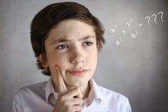 Έξυπνο αγόρι εφήβων που σκέφτεται τη δύσκολη εξίσωση Στοκ φωτογραφίες με δικαίωμα ελεύθερης χρήσης