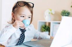 Έξυπνο κορίτσι μικρών παιδιών με τα γυαλιά που πίνει τον καφέ χρησιμοποιώντας ένα lap-top Στοκ φωτογραφία με δικαίωμα ελεύθερης χρήσης
