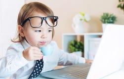 Έξυπνο κορίτσι μικρών παιδιών με τα γυαλιά που πίνει τον καφέ χρησιμοποιώντας ένα lap-top Στοκ εικόνα με δικαίωμα ελεύθερης χρήσης