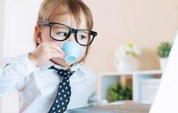 Έξυπνο κορίτσι μικρών παιδιών με τα γυαλιά που πίνει τον καφέ χρησιμοποιώντας ένα lap-top Στοκ Φωτογραφία