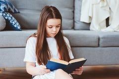 έξυπνο κορίτσι παιδιών που διαβάζει το ενδιαφέρον βιβλίο στοκ φωτογραφία