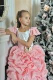 Έξυπνο κορίτσι σε ένα ρόδινο φόρεμα από την εστία Στοκ Εικόνες