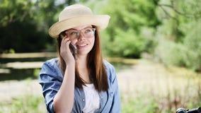 Έξυπνο κορίτσι brunette σε ένα καπέλο που μιλά στο τηλέφωνο υπαίθρια απόθεμα βίντεο