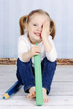Έξυπνο μικρό κορίτσι που κρατά τα μεγάλα κραγιόνια Στοκ Εικόνα