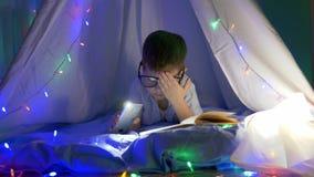 Έξυπνο παιδί στα γυαλιά με το διαθέσιμο βιβλίο ανάγνωσης χεριών φακών πρίν πηγαίνει στο κρεβάτι στο σκοτάδι απόθεμα βίντεο