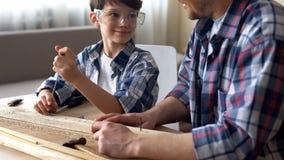 Έξυπνο προσεκτικό αγόρι που εργάζεται με το κατσαβίδι και το ξύλο, γιος διδασκαλίας πατέρων στοκ φωτογραφίες