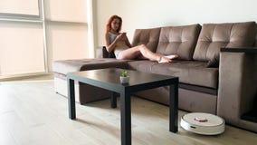 Έξυπνο σπίτι Ο καθαρισμός της ρομποτικής ηλεκτρικής σκούπας του σπιτιού, όταν βάσισαν οι γυναίκες στους καναπέδες παίζει τα κινητ απόθεμα βίντεο