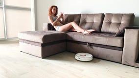 Έξυπνο σπίτι Ο καθαρισμός της ρομποτικής ηλεκτρικής σκούπας του σπιτιού, όταν βάσισαν οι γυναίκες στους καναπέδες παίζει τα κινητ φιλμ μικρού μήκους