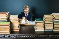 Έξυπνο σχολικό αγόρι που διαβάζει ένα βιβλίο στη βιβλιοθήκη Στοκ Εικόνες