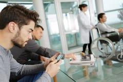 Έξυπνο τηλέφωνο χρήσης ατόμων περιμένοντας στην κλινική Στοκ εικόνα με δικαίωμα ελεύθερης χρήσης