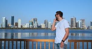 Έξυπνο τηλεφωνικό άτομο που καλεί το κινητό τηλέφωνο στην πόλη Όμορφο νέο επιχειρησιακό άτομο που μιλά στο χαμόγελο smartphone ευ απόθεμα βίντεο