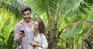 Έξυπνο τηλεφωνικό αγκάλιασμα κυττάρων χρήσης ζεύγους που μιλά πέρα από τους φοίνικες, το νεαρό άνδρα και τη γυναίκα που κουβεντιά απόθεμα βίντεο