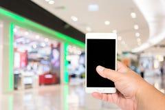 Έξυπνο τηλέφωνο λαβής ατόμων θολωμένος των ανθρώπων που ψωνίζουν στο υπόβαθρο λεωφόρων αγορών Στοκ Φωτογραφία