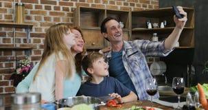 Έξυπνο τηλέφωνο κυττάρων χρήσης πατέρων που παίρνει το πορτρέτο Selfie του ευτυχούς οικογενειακού μαγειρέματος στην κουζίνα μαζί  απόθεμα βίντεο