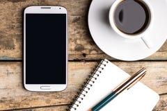 Έξυπνο τηλέφωνο με το σημειωματάριο και το φλυτζάνι του ισχυρού καφέ Στοκ Φωτογραφία
