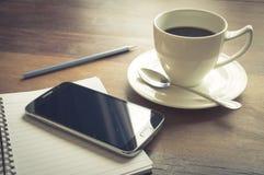 Έξυπνο τηλέφωνο με το φλυτζάνι, το βιβλίο και το μολύβι καφέ Στοκ Εικόνες