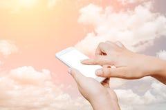 Έξυπνο τηλέφωνο οθόνης λαβής και αφής χεριών γυναικών στο υπόβαθρο σύννεφων Στοκ Εικόνα