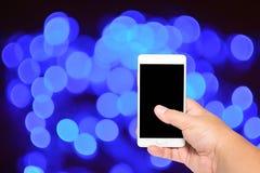 Έξυπνο τηλέφωνο οθόνης λαβής και αφής χεριών γυναικών στο υπόβαθρο bokeh Στοκ Φωτογραφίες