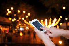 Έξυπνο τηλέφωνο οθόνης λαβής και αφής χεριών, θολωμένο στο περίληψη pho στοκ εικόνα