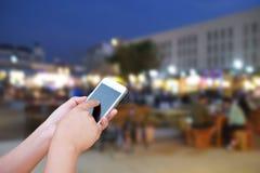 Έξυπνο τηλέφωνο οθόνης λαβής και αφής χεριών, στη θολωμένη φωτογραφία του peop Στοκ Φωτογραφία