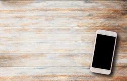 Έξυπνο τηλέφωνο στον παλαιό ξύλινο πίνακα στοκ εικόνες