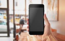 Έξυπνο τηλέφωνο στο χέρι ατόμων Καφετερία στο υπόβαθρο Στοκ εικόνα με δικαίωμα ελεύθερης χρήσης