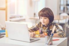 Έξυπνο όμορφο αγόρι που γράφει στις κολλώδεις σημειώσεις στοκ φωτογραφία