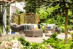 Έπιπλα κήπων ινδικού καλάμου και κρεμώντας καρέκλα στο ξύλινο πεζούλι του χ στοκ εικόνες