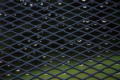 Έπιπλα κήπων που ψεκάζονται με τις πτώσεις βροχής Στοκ εικόνες με δικαίωμα ελεύθερης χρήσης