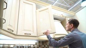 Έπιπλα κουζινών αγοράς νεαρών άνδρων Τύπος που επιλέγει το ντουλάπι για το νέο σπίτι του φιλμ μικρού μήκους